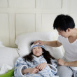Young man taking care of sick woman in bed — Stock Photo