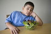 Olycklig preadolescent pojke sitter vid skrivbord med sallad — Stockfoto