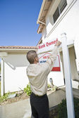 """Young Man Putting Up """"For Sale Notice"""" — Stock Photo"""