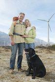 Altes paar mit hund in der nähe von windparks — Stockfoto