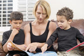 Mother reading book with two children — Stockfoto