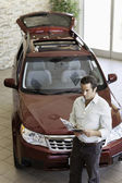 Mid-adult man reading document in front of luxury car in show room — Stock Photo