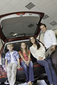Portrait of happy family sitting at back of their new car — Stock Photo