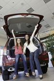 Low angle view of happy mother and daughter sitting at back of car — Stock Photo