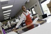 Manual worker taking large printouts — Stock Photo