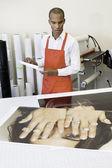 Člověk pracující v tiskařském stroji s výtisky fotografií na stole — Stock fotografie