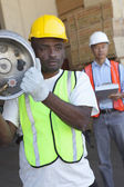 Warehouse worker carrying cylinder with manager in background — Stock Photo