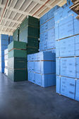 Blue boxes piled up of in warehouse — Stock Photo