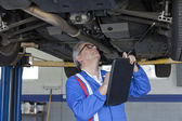 Mechanic scrutinizing the car and writing down something on clipboard — Stock Photo