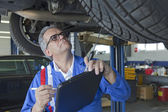 Mechanic analyzing car engine at auto repair shop — Stock Photo