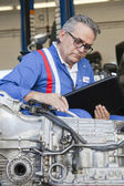 Senior mechanic analyzing car engine and holding clipboard — Stock Photo