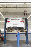 механик, проверка под автомобиль на подъемнике — Стоковое фото