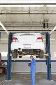Mechanik sprawdzanie pod samochód na podnośniku — Zdjęcie stockowe
