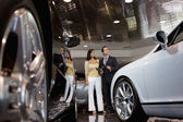 Woman standing with auto salesman in car showroom — Stock Photo