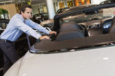 Car salesperson leaning on car — Stock Photo