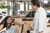 Coppia controllando le nuove vetture nello showroom di concessionaria — Foto Stock