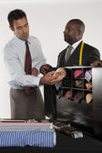Man selecting neckwear while shop owner standing besides him — Stock Photo