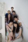 Group portrait of friends sitting in stairway — Stock Photo