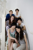 Group portrait of young friends sitting in stairway — Stock Photo