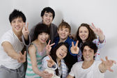 Group portrait of young friends showing peace sign — Stock Photo