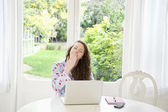 Giovane donna seduta davanti al computer portatile di scarico — Foto Stock