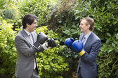 Two young men in suits stage a mock boxing match — Stock Photo