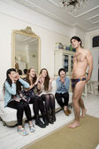 Male stripper posing in front of women — Stok fotoğraf