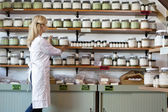 Senior female employee arranging spice jars on shelf — Stock Photo
