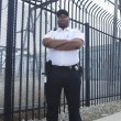 Stock Photo: Security Guard Standing In Front Of Prison Fence