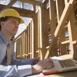 Architect Working On Laptop At Site — Stock Photo #24460389