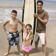 Man holding surfboard with children — Stock Photo