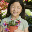 Young girl holding potted flowers — Stock Photo
