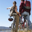 Couple with mountain bikes by the lake — Stock Photo