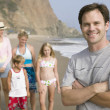 Man on beach with family — Stockfoto