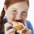 Stock Photo: Overweight girl eating pastry