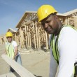 Stock Photo: Construction workers stacking timber