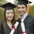 Two graduates holding diplomas — Stock Photo