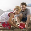 Stock Photo: Father building sandcastle with son