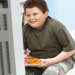 Overweight boy eating carrot sticks — Stock Photo