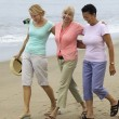 Women walking on beach — Stockfoto