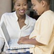 Son using laptop with mother — Stock Photo