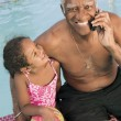 Senior man sitting by pool with granddaughter — Stock Photo #33797993