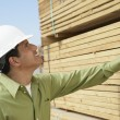 Construction worker inspecting lumber — Stock Photo