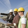 Construction workers with plans — Stock Photo #33798683