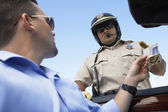 Man handing licence to police officer — Stock Photo