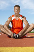 Male athlete warming up on racing track — Stock Photo