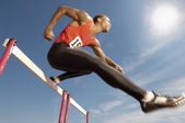 Athlete jumping over a hurdles — Stock Photo
