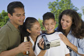 Boy looking at camcorder with family — Stock Photo