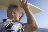 Surfer carrying surfboard — Stock Photo