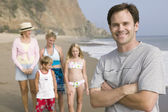 Man on beach with family — Stock Photo
